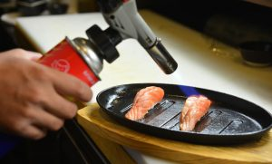 chef using a torch burn on salmon sushi