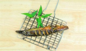 Grilled catfish and gridiron on wooden background