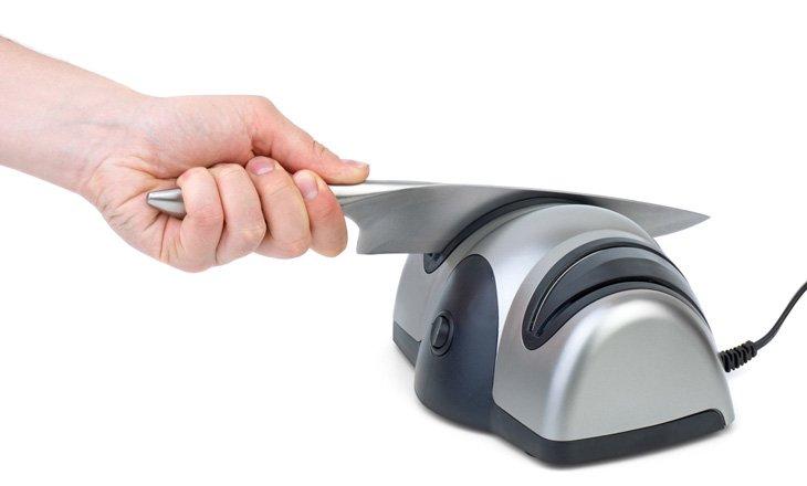 Knife sharpening (Using electrical sharpener). White background