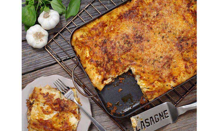Photo of a freshly baked lasagna, sitting on an old wooden table with a portion cut out and waiting on a plate.