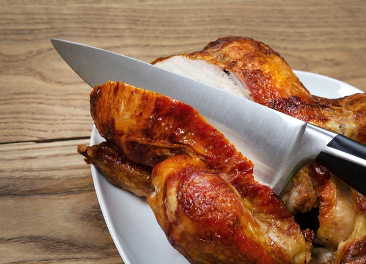 Roasted Chicken being Sliced by Large Sharp Kitchen Knife