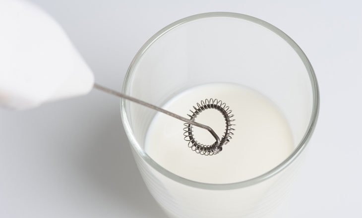 closeup milk frother and half cup of milk